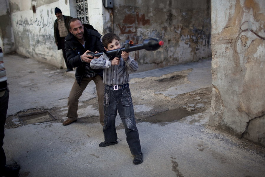 Rodrigo Abd Pulitzer-winning photo: A man teaches Bilal, 11, how to use a toy rocket propelled grenade in Idlib, northern Syria, March 4, 2012.