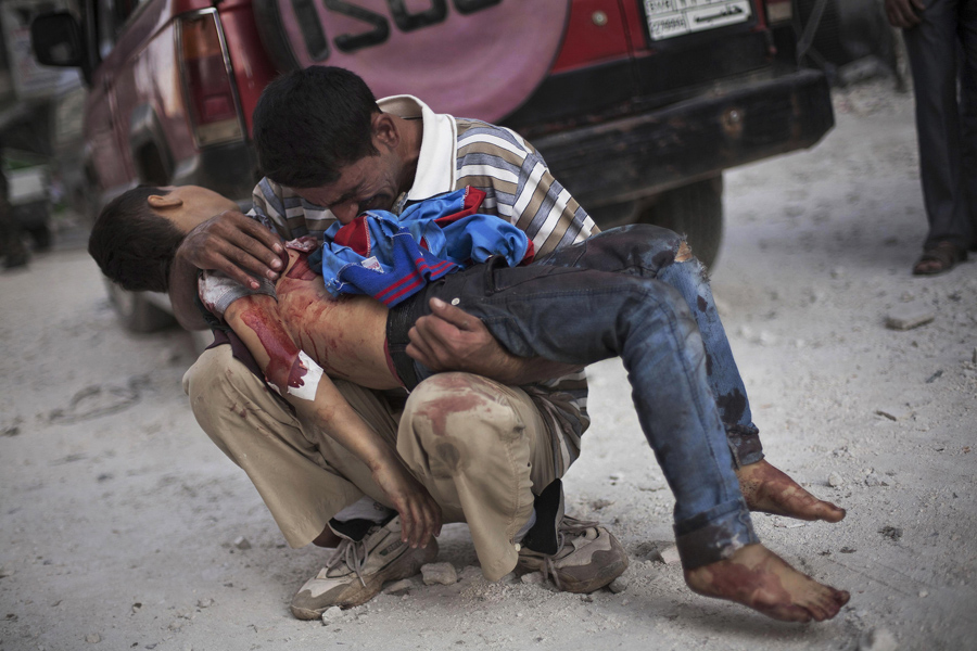 Manu Brabo Pulitzer-winning photo: A Syrian man cries while holding the body of his son near Dar El Shifa hospital in Aleppo, Syria, Oct. 3, 2012. The boy was killed by the Syrian army.